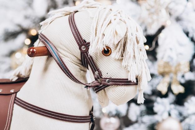 Babyschaukel - pony auf dem hintergrund eines weihnachtsbaumes