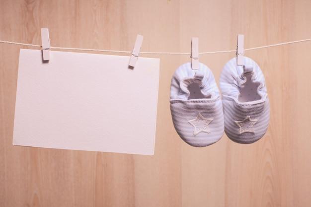 Babyschuhe am seil befestigt und leere karte für grüße