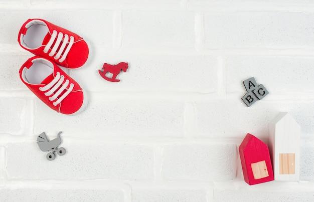 Babyschuhe und holzspielzeug auf weißem backstein