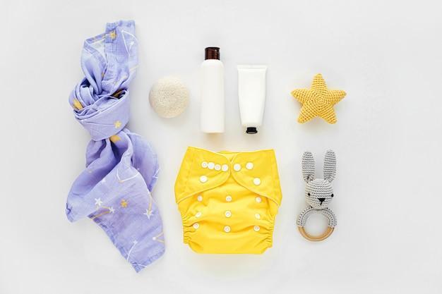 Babyset aus stoffwindel und musselin-wickeldecke und kindersachen. umweltfreundliche stoffwindeln für neugeborene. flache lage, ansicht von oben