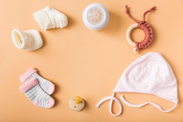 Babysocke; paar wollschuhe; schnuller; deckel; milchflasche; spielzeug auf einem orangefarbenen hintergrund