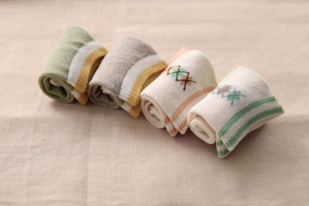 Babysocken, die an der wäscheleine auf hölzernem hintergrund hängen