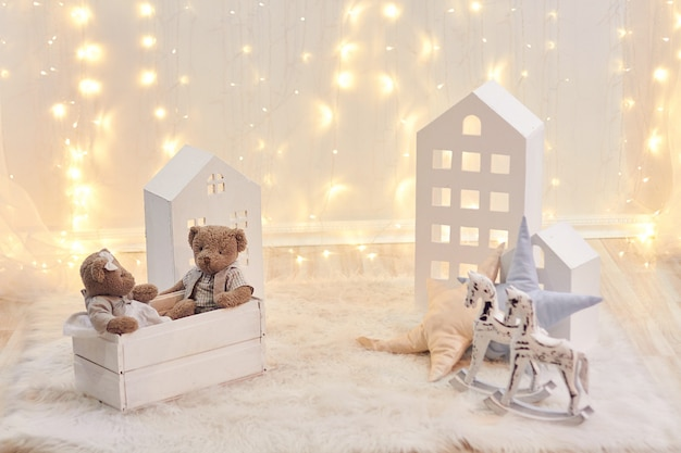 Babyspielwaren und spielzeughaus auf einem hintergrund von weihnachtslichtern. feiertagsdekor