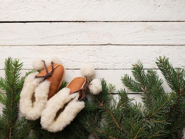 Babyweihnachtsstiefel und grüner baum auf weißem holz, winterkinderkarte, copyspace