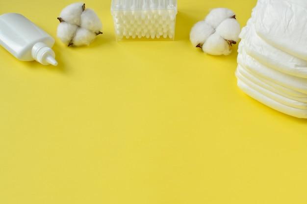 Babywindeln mit wattestäbchen, puder, talkumpuder und trockener baumwolle auf gelbem hintergrund, draufsicht. es gibt eine kopie des ortes.