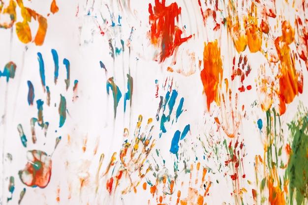 Babyzeichnung mit aquarell auf weißem wandhintergrund. werke der abstrakten kinderskizze. farbige kinderhandabdrücke und auf bildern unordentlich bespritzt. einzigartige hintergründe für kreativität und tapeten