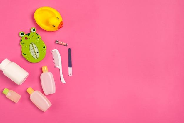 Babyzubehör für bad mit ente auf rosa hintergrund. ansicht von oben. platz kopieren. stillleben. flach legen
