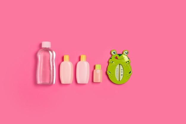 Babyzubehör für bad mit frosch auf rosa hintergrund. ansicht von oben. platz kopieren. stillleben. flach legen