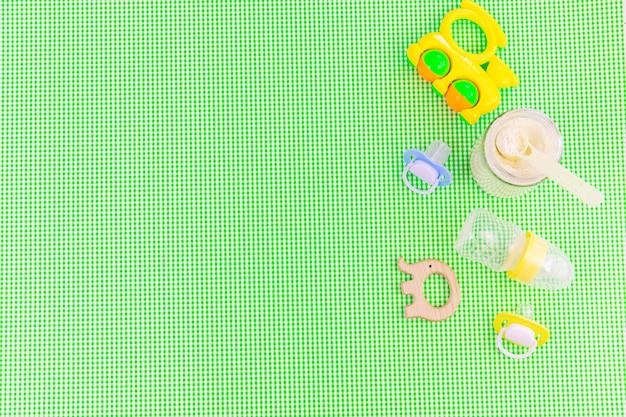 Babyzubehör und -nahrung auf grünem hintergrund. selektiver fokus.baby