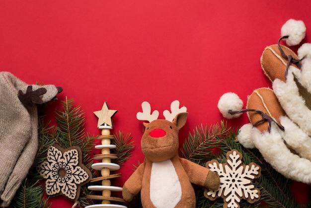 Babyzubehörhut und -stiefel, hölzerne spielwaren und weihnachtstannenbaum auf rot, copyspace. konzept der ferien in der kindheit