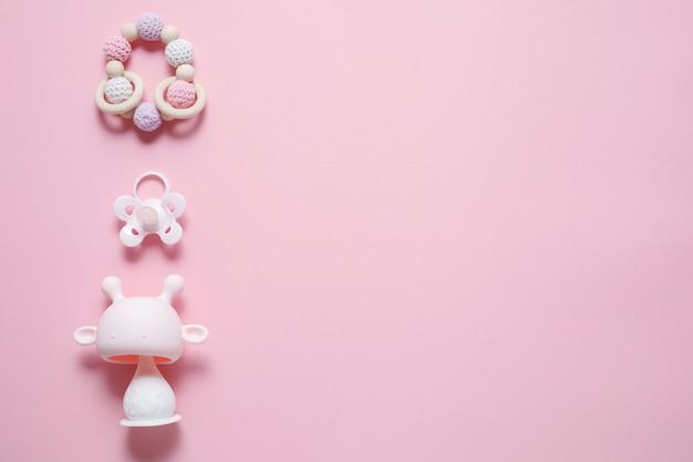 Babyzubehörkonzept: beißring, raupenspielzeug und babyschnuller, über rosa hintergrund mit kopierraum, draufsicht, flache lage