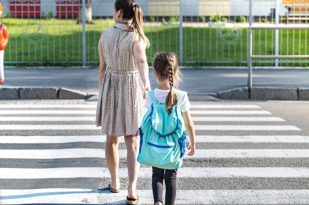 Back to school bildungskonzept mit mädchen, grundschülern, rucksäcken zum unterricht tragend