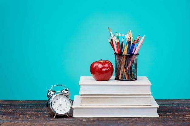Back to school-konzept. bücher, buntstifte und uhr