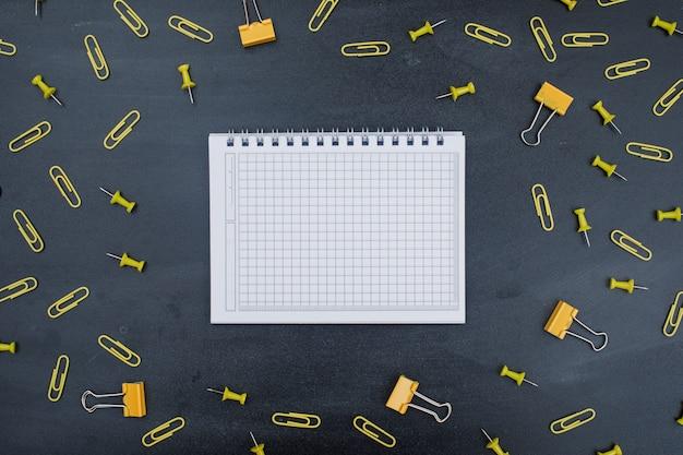 Back to school-konzept mit notizbuch, büroklammern, binderclips, stecknadeln auf grauem hintergrund.