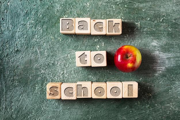 Back to school slogan auf holzwürfeln grüner tafelhintergrund und reifer apfel sind ein symbol des wissens