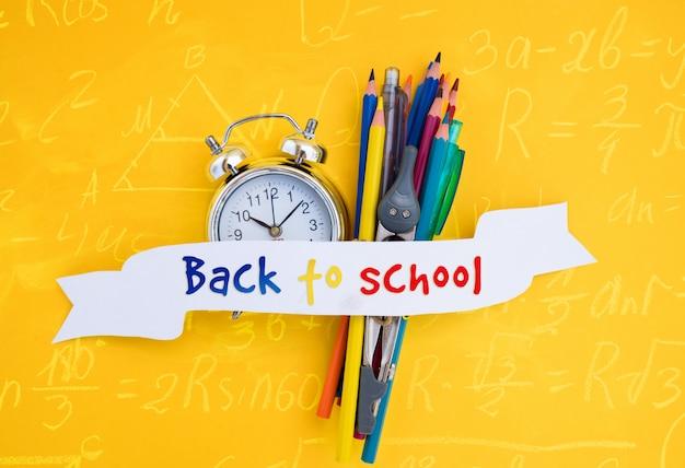 Back to school wörter auf weißem band über uhr und schulmaterial