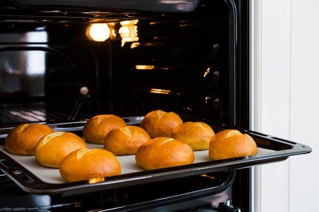 Backblech mit frischen hausgemachten brötchen im ofen.