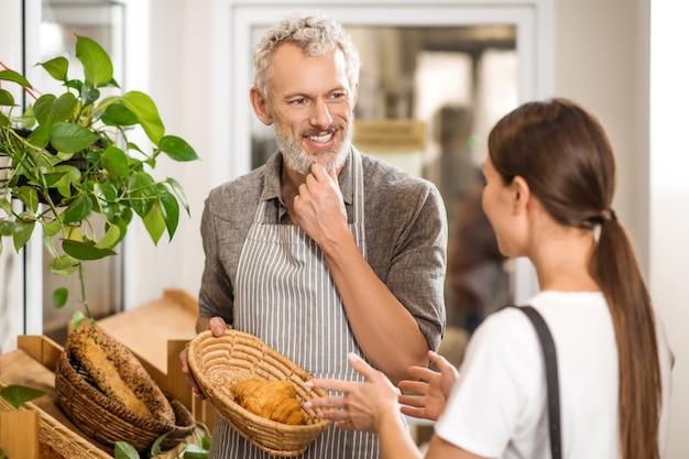 Backen, interesse. erwachsener interessierter lächelnder mann in der schürze, die croissant zum sprechenden kunden zeigt gegenüber