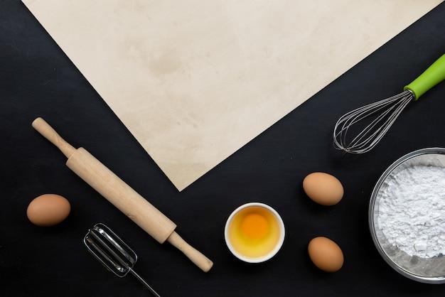 Backen kochen zutaten auf schwarzem hintergrund. draufsicht