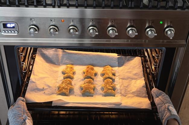 Backen lebkuchenmann im ofen, frau, die hausgemachte lebkuchenmannplätzchen im ofen macht