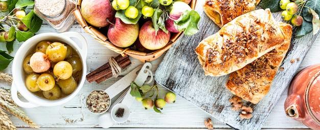 Backen mit apfel, frisch gebackenem apfel und zimtschnecken aus blätterteig auf einem weißen holztisch. draufsicht, rustikaler stil, kopierraum.