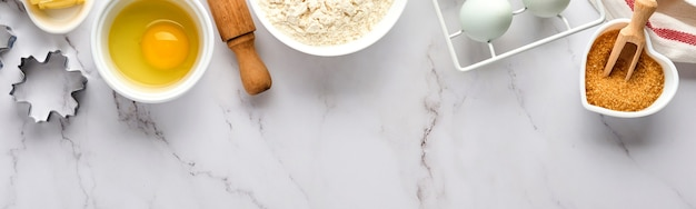 Backen mit mehl, eiern, küchenwerkzeugen, utensilien und keksformen auf weißem marmortisch