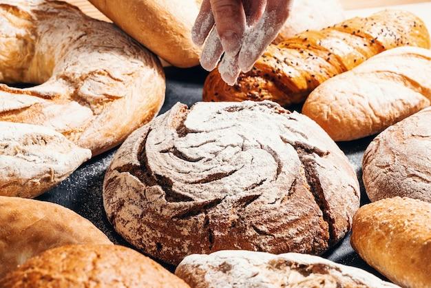 Backen nahaufnahme appetitliche brötchen mit mehl bestreut auf einem schwarzen holztisch backwaren
