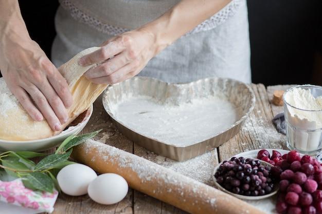 Backen sie einen obstkuchen in form eines herzens. hände verteilen den teig auf dem kuchen. kochen