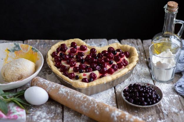 Backen sie einen obstkuchen in form eines herzens. köstlicher hausgemachter kuchen zum selbermachen. kochen.märz 8. grußkarte für den 8. märz.