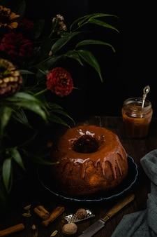 Backen sie kuchen mit gewürzen, zimt, sternanis, muskatnuss und karamellsoßenglasur auf dunklem holztisch zusammen