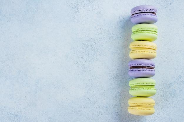 Backen sie macaron oder makrone auf hellblauem hintergrund von oben zusammen