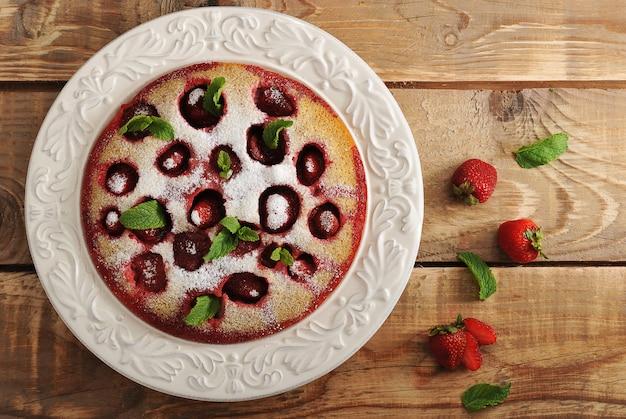 Backen sie mit erdbeeren in der platte auf holzoberfläche zusammen