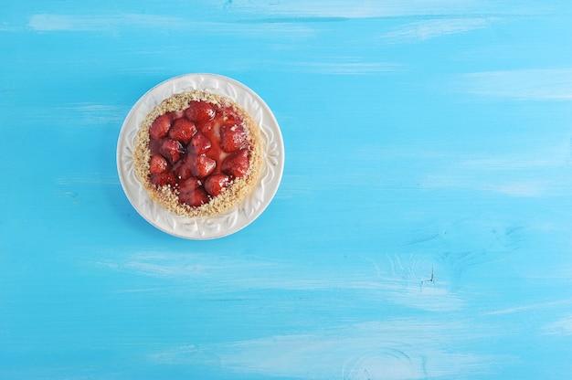 Backen sie mit erdbeeren und gelee auf einem blauen hölzernen zusammen
