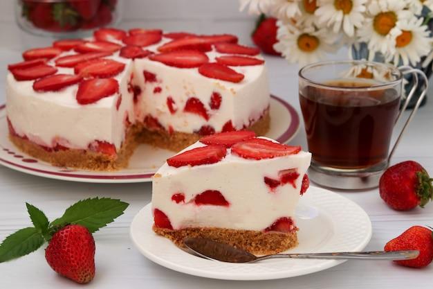Backen sie mit erdbeeren zusammen, ohne das backen, das auf einer platte auf einem weiß gelegen ist