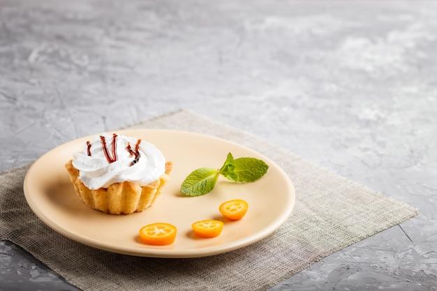 Backen sie mit schlagsahne auf einer hellbraunen platte mit scheiben der japanischen orange und tadellosen blättern zusammen
