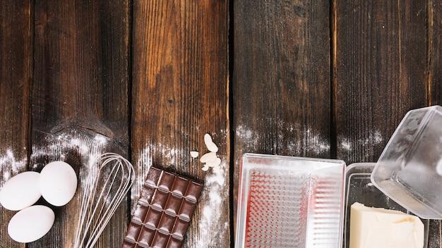 Backende kuchenzutaten mit küchengerät auf hölzerner planke