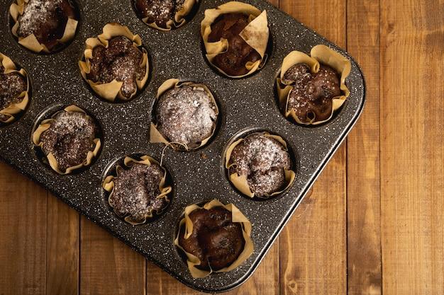Backform mit leckeren schokoladenmuffins auf dem holztisch