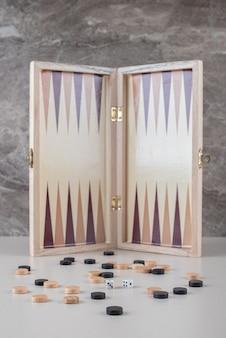 Backgammonbrett steht aufrecht hinter verstreuten stücken und würfeln auf marmor