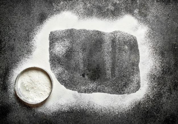 Backhintergrund der rahmen besteht aus mehl mit einem sieb