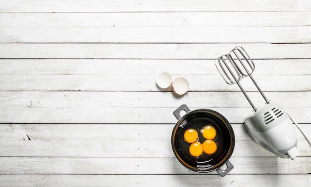 Backhintergrund. frische eier mit einem mixer. auf einem weißen hölzernen hintergrund.