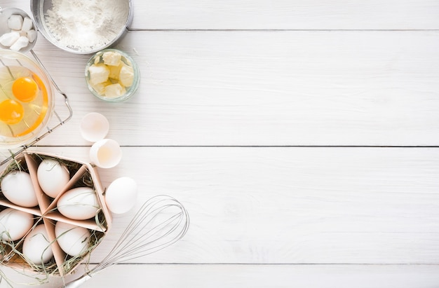Backhintergrund. kochzutaten für teig, eier und butter auf weißem rustikalem holz. draufsicht, rezept oder kochkurse.