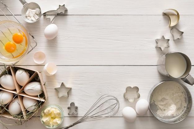 Backhintergrund. kochzutaten für teig und gebäck, eier, mehl und ausstecher auf weißem rustikalem holz. draufsicht