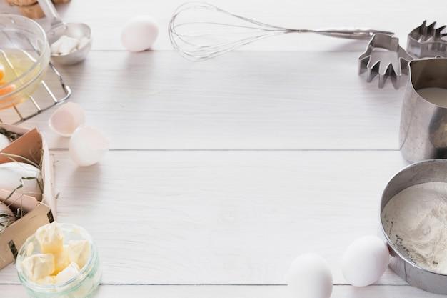 Backhintergrund. kochzutaten für teig und gebäck, eigelb, mehl auf weißem rustikalem holz.