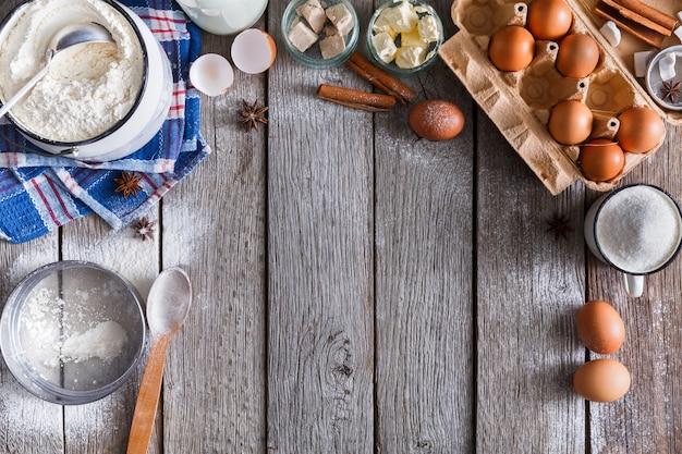 Backhintergrund. kochzutaten für teig- und gebäckherstellung auf rustikalem holz. draufsicht