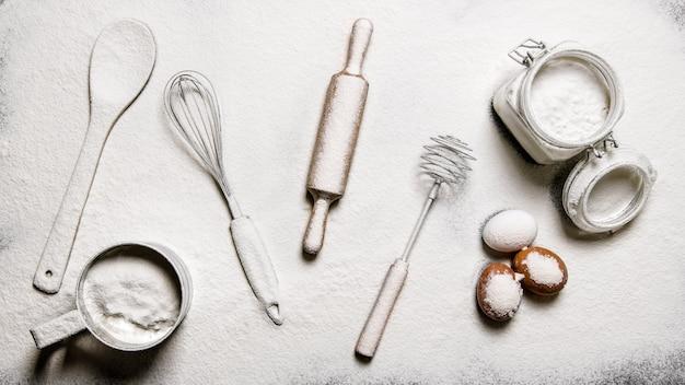 Backhintergrund. mehl, eier und verschiedene werkzeuge - schläger, spatel, nudelholz und ein sieb. auf dem tisch mit mehl. draufsicht