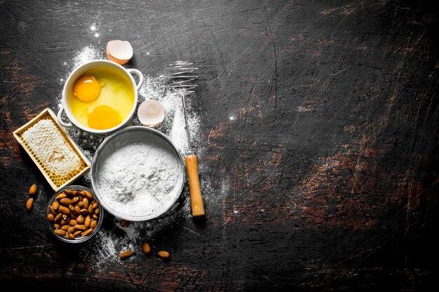 Backhintergrund. mehl mit honig, nüssen und eiern. auf dunklem rustikalem hintergrund