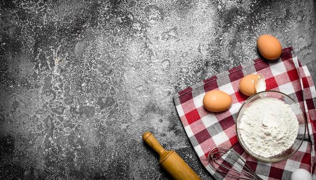 Backhintergrund mehl und frische eier zum backen auf rustikalem hintergrund