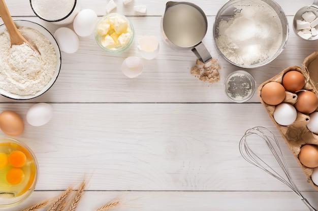 Backhintergrund mit kopierraum. kochzutaten für teig und gebäck, eier, mehl und butter auf weißem rustikalem holz. draufsicht