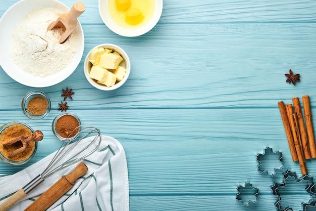 Backhintergrund mit zutaten für die herstellung von lebkuchenmehl, eiern, küchengeräten, utensilien und keksformen auf blauem holztisch. ansicht von oben. flacher lay-stil. attrappe, lehrmodell, simulation. weihnachtsbäckerei.