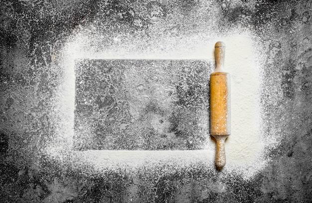 Backhintergrund rahmen des gesiebten mehls mit einem nudelholz auf rustikalem hintergrund